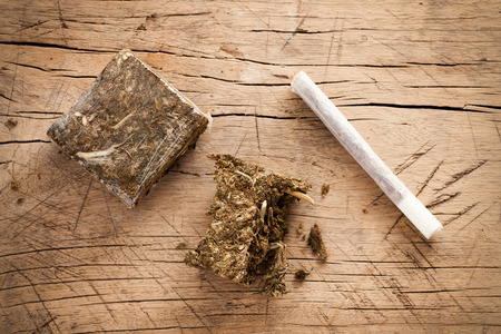 hashish: weed marijuana hashish roll wood background herb health medicine alternative