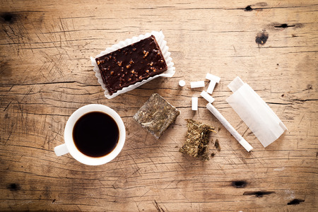 hashish: weed marijuana hashish roll wood background herb health medicine alternative coffee chocolate brownie
