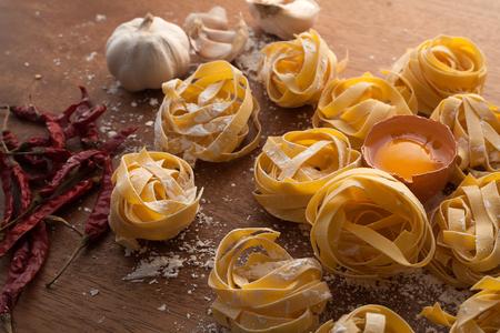alfredo: fettuccine pasta italian food still life rustic wood background tagliatelle alfredo garlic chili pepper  yolk