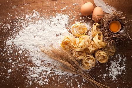food still: fettuccine pasta italian food still life rustic flat lay wood background tagliatelle alfredo yolk egg