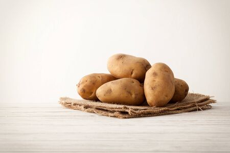 russet potato: potato ingredient raw rustic still life white wood background