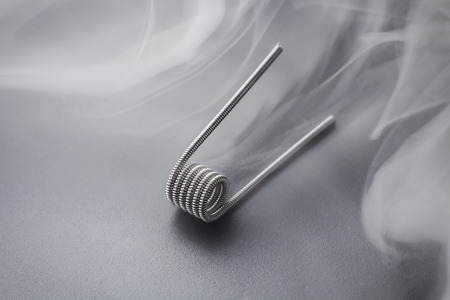 Clapton coil for vaping on a black background smoke macro closeup wire steel