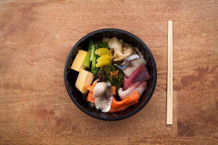 tekka: Japanese food Tekka Don take away on wooden background raw tuna salmon otoro seaweed rice