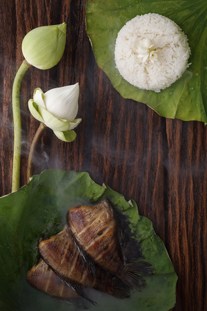 thai food rice and dried salted damsel fish fried with flower lotus jasmine decoration on wooden background beautiful flat lay still life rustic asia