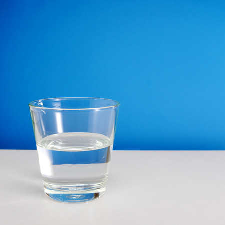 half full: Half empty or half full glass of water on white table on blue background. 1