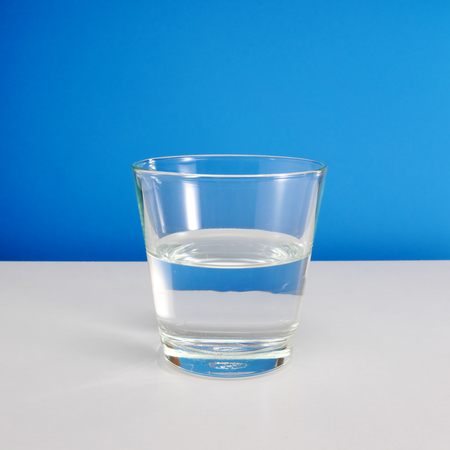 glass half full: Half empty or half full glass of water on white table on blue background. 2 Stock Photo