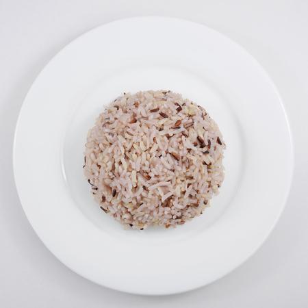 De gekookte bruine rijst op de witte plaat.