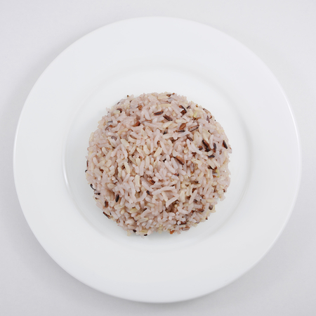 rice plate: The cooked brown rice on the white plate.