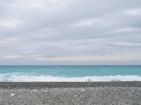 gravel: The sand gravel beach with a wave of sea water. Stock Photo