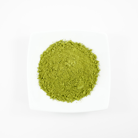 The Japanese matcha green tea powder on the mini white dish.