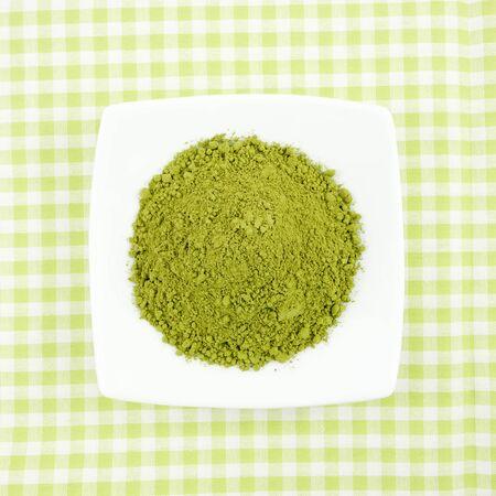 green powder: The Japanese matcha green tea powder on the mini white dish on green cotton fabric.