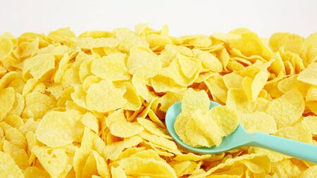 maiz: The close up of tasty golden corn flakes with the green plastic spoon.