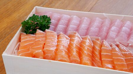 The close up of Japanese fresh sashimi salmon and fatty tuna in white lunch box set.