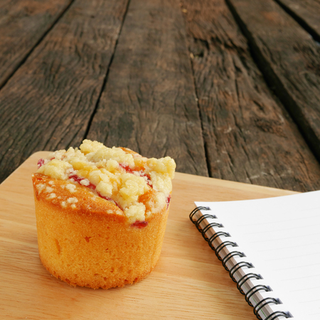 blueberry muffin: The delicious blueberry muffin and small note book on the old deep brown planks.