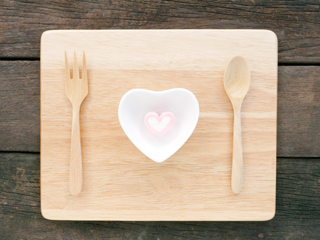 ceramic heart: The ceramic heart shaped bowl and pink marshmallow and wooden spoon with fork on the wooden board and old deep brown planks background for Valentines day.