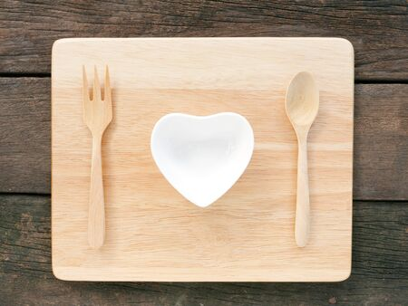 ceramic heart: The ceramic heart shaped bowl and wooden spoon with fork on the wooden board and old deep brown planks background for Valentines day. Stock Photo