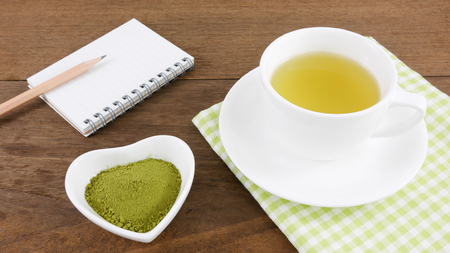 green herbs: The Japanese matcha green tea powder on ceramic heart shaped bowl and cup of hot green tea and note book with pencil on wooden planks.