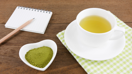 ceramic heart: The Japanese matcha green tea powder on ceramic heart shaped bowl and cup of hot green tea and note book with pencil on wooden planks.