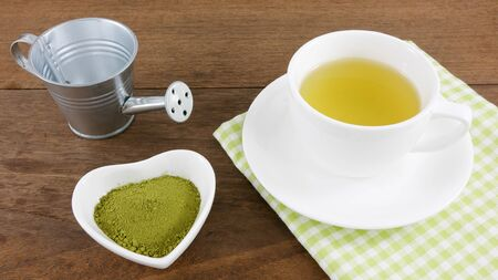 ceramic heart: The Japanese matcha green tea powder on ceramic heart shaped bowl and cup of hot green tea with cotton fabric on wooden planks.