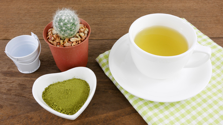 ceramic heart: The Japanese matcha green tea powder on ceramic heart shaped bowl and cup of hot green tea with cotton fabric and little cactus in plant pot on wooden planks.