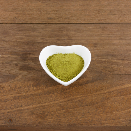 ceramic heart: The Japanese matcha green tea powder on ceramic heart shaped bowl on wooden planks.
