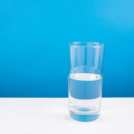 half full: Half empty or half full glass of water on white table. For positive thinking when see the glass is half full. Stock Photo