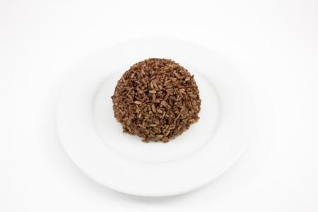 plato del buen comer: El arroz cocinado marr�n oscuro en el plato blanco para una buena salud.