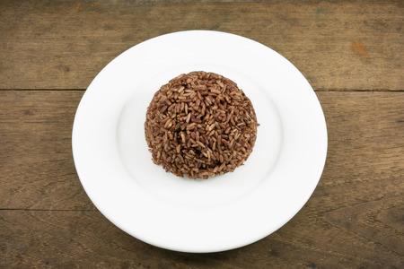 plato del buen comer: El arroz cocinado marrón oscuro en la placa blanca sobre tablones de madera viejos para la buena salud.