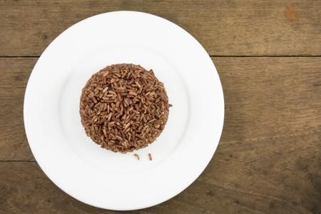 plato del buen comer: El arroz cocinado marr�n oscuro en la placa blanca sobre tablones de madera viejos para la buena salud.