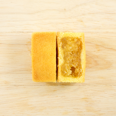 taiwanese: The tasty Taiwanese pineapple pastry cake with egg yolk on the wooden plank.
