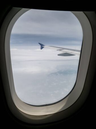View of airplane wing and blue sky from airplane window. Reklamní fotografie