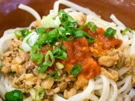 The close up of tasty tomato sauce dry noodles with minced pork.