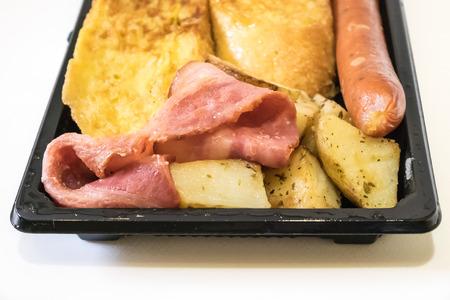 The close up of delicious breakfast set on black plastic tray. (becon, sausage, potato, omelette) Reklamní fotografie