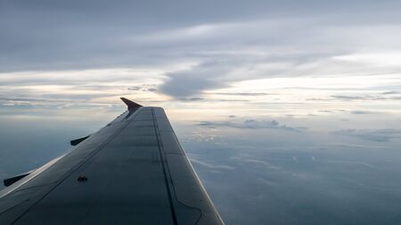 The airplane wing on the beautiful cloudy and sky at early in the evening. Reklamní fotografie