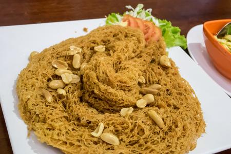 The delicious Thai crispy catfish salad on white plate.