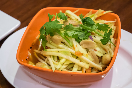 The delicious green mango salad for Thai crispy catfish on small orange bowl.
