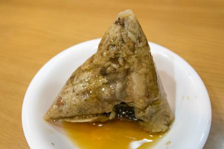 The close up of Chinese sticky rice dumpling (Zongzi) on small white plate. Reklamní fotografie
