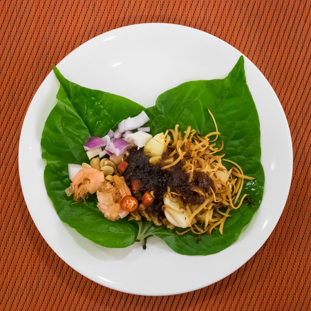The close up of Thai appetizer leaf wrapped with herbs (Miang Kham) on white plate. Reklamní fotografie
