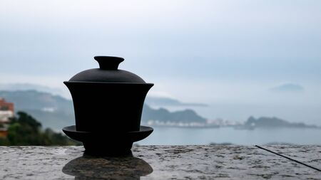 The classic Taiwanese tea cup on top of wall with sea view at Jiufen old street in Taiwan. Stock Photo