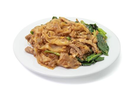 The close up of Fried Noodle with soy sauce on white plate on white background.
