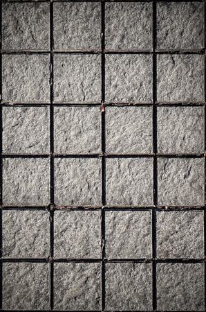 cell block: gray stone tiles background and texture with sun ray color with vignette to focus at the center Stock Photo