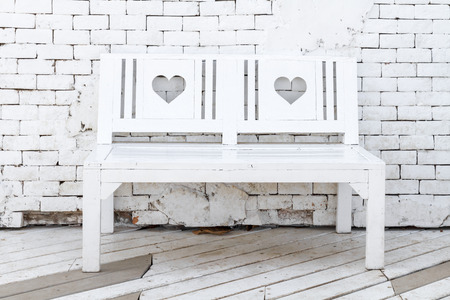 timber bench seat: White wooden bench against white brick wall