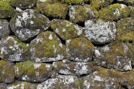 stacked stone: Uneven stacked stone wall background Stock Photo