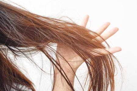 Peigner avec brosse et tire les cheveux longs. Préparation quotidienne à la recherche de beaux cheveux longs et ébouriffés, tenant les cheveux en désordre, non brossés, en mains. Dommages aux cheveux, santé et beauté Concept.