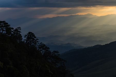 transcendence: sun rays breaking through the clouds over a mountain landscape and forest in thailand