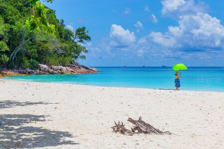 umbella: Adult lady with yellow umbella walking in the beach , Tachai Island , Thailand Stock Photo