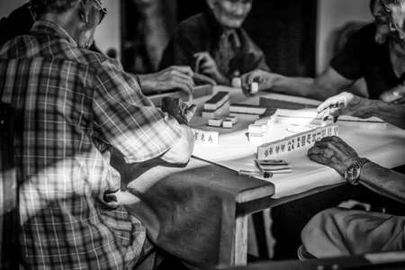 mahjong: Old Chinese people playing Mah-jong chinese card games in film look with grain Stock Photo