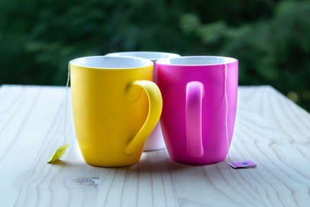 Three multi coloured mugs with tea with teabags string showing.
