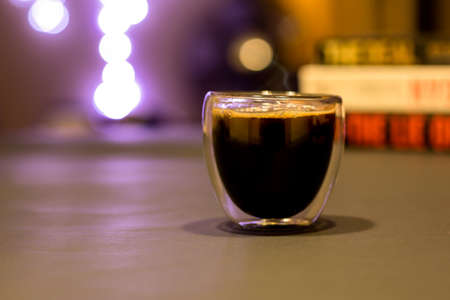 Hot steamy cup of black coffee with out of focus lights background