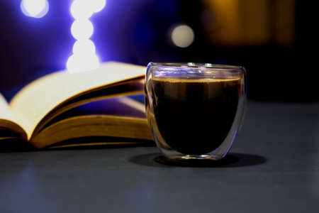 Hot black coffe in a glass cup with an open book